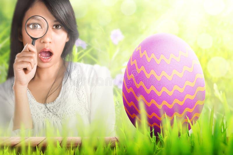 Молодая азиатская женщина с увеличителем находя пасхальное яйцо стоковые изображения