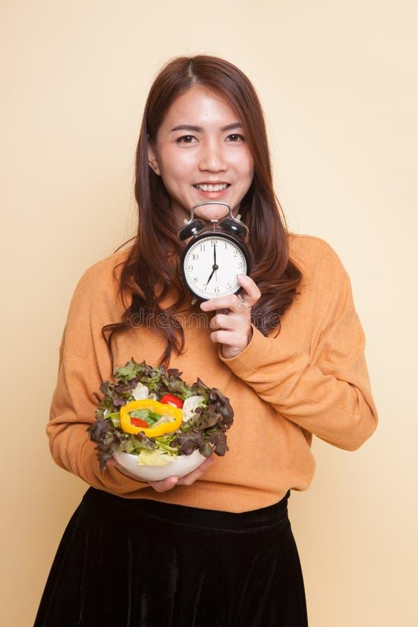 Молодая азиатская женщина с часами и салатом стоковые изображения rf