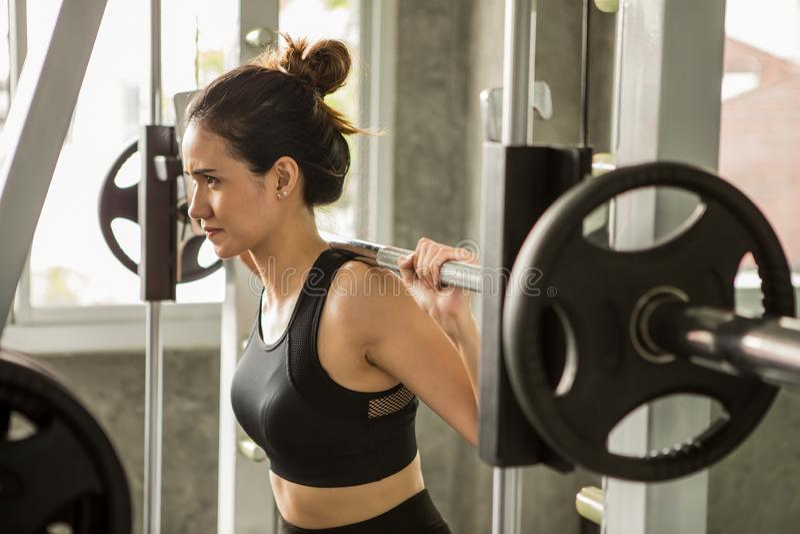 молодая азиатская женщина фитнеса в sportswear работая строя мышцы поднимая вес со штангой в спортзале разминка девушки спорта зд стоковое фото