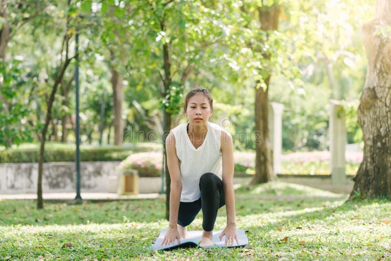 Молодая азиатская йога женщины outdoors держит затишье и размышляет пока практикующ йогу для того чтобы исследовать внутренний ми стоковое фото