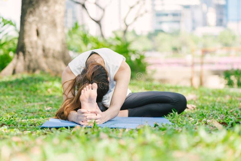 Молодая азиатская йога женщины outdoors держит затишье и размышляет пока практикующ йогу для того чтобы исследовать внутренний ми стоковые фото