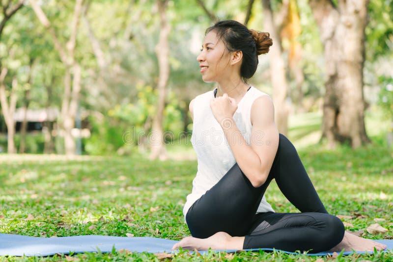 Молодая азиатская йога женщины outdoors держит затишье и размышляет пока практикующ йогу для того чтобы исследовать внутренний ми стоковое изображение