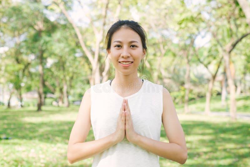 Молодая азиатская йога женщины outdoors держит затишье и размышляет пока практикующ йогу для того чтобы исследовать внутренний ми стоковая фотография rf