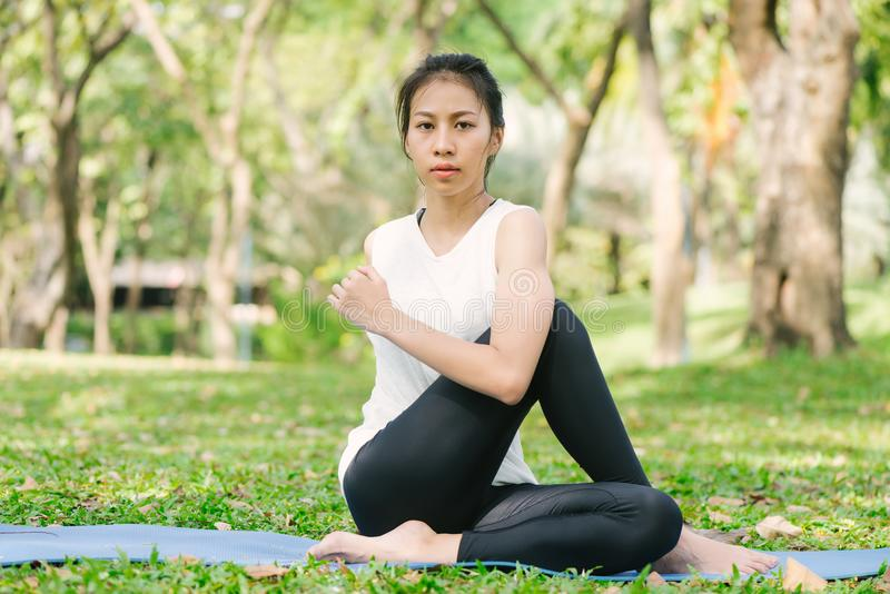 Молодая азиатская йога женщины outdoors держит затишье и размышляет пока практикующ йогу для того чтобы исследовать внутренний ми стоковая фотография