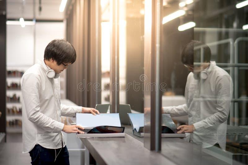 Молодая азиатская книга отверстия студента университета человека в библиотеке стоковые изображения rf