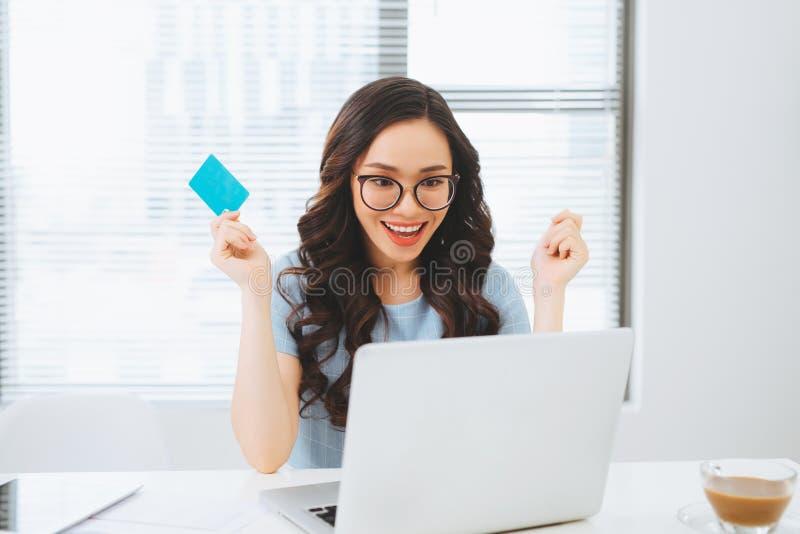 Молодая азиатская коммерсантка используя кредитную карточку для на-линии оплаты стоковое фото