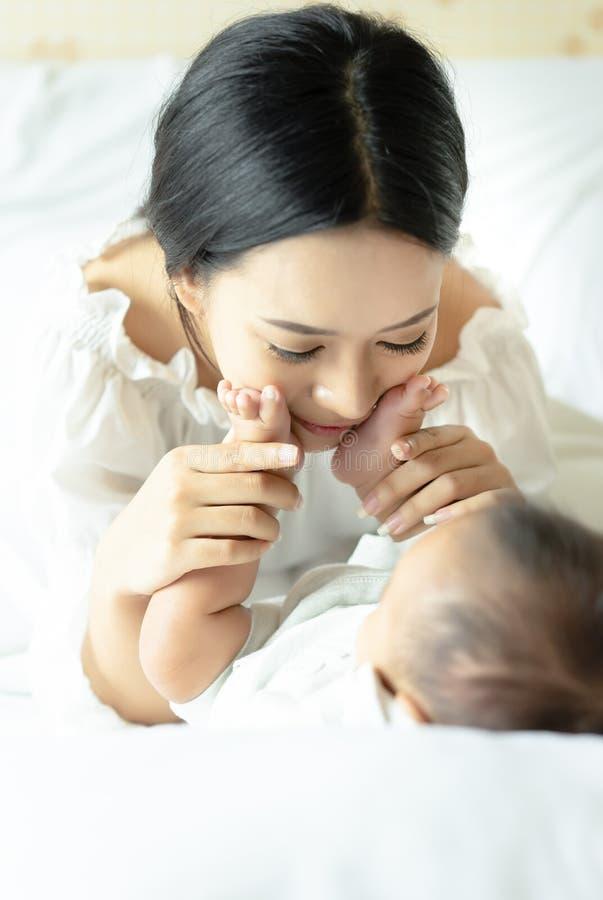 Молодая азиатская мать играя с ее newborn дочерью младенца и стоковое фото rf