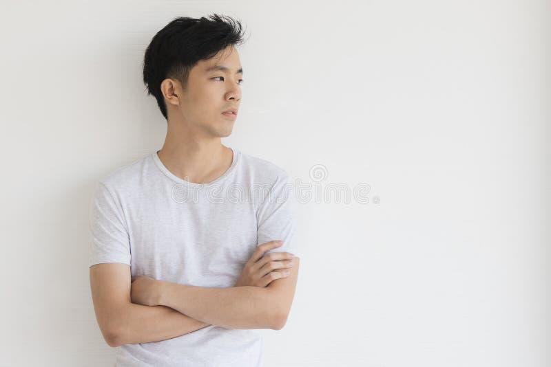 Молодая азиатская модель человека в футболке пересекла руку стоковое изображение