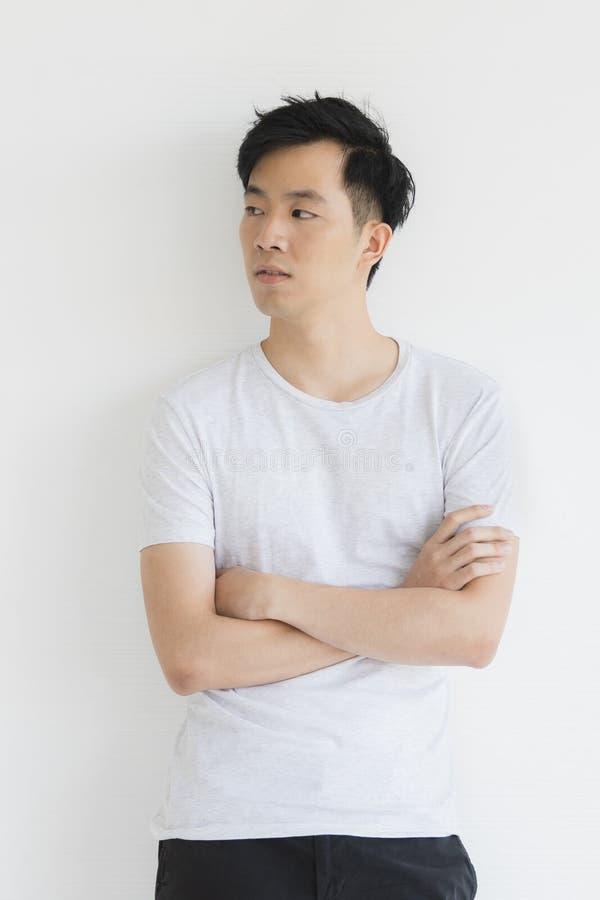Молодая азиатская модель человека в футболке пересекла руку стоковое изображение rf