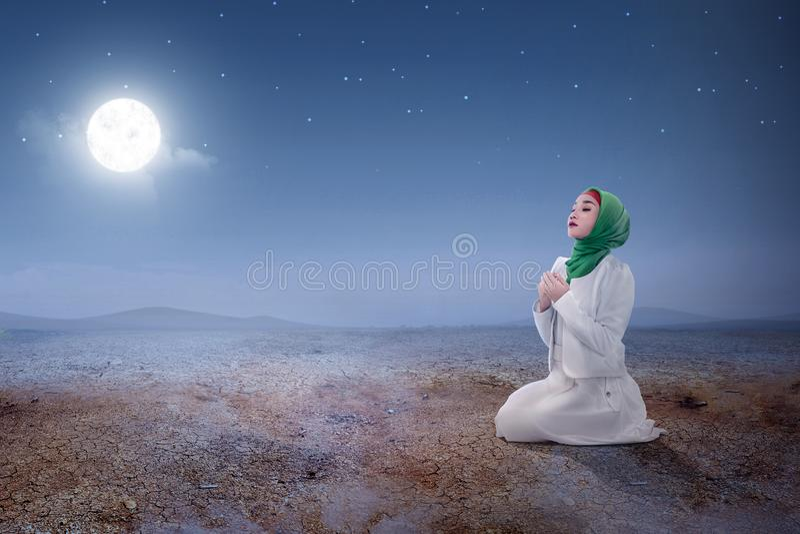 Молодая азиатская мусульманская женщина сидя внутри молит положение пока поднятые руки и молить на песчанной дюне стоковое изображение