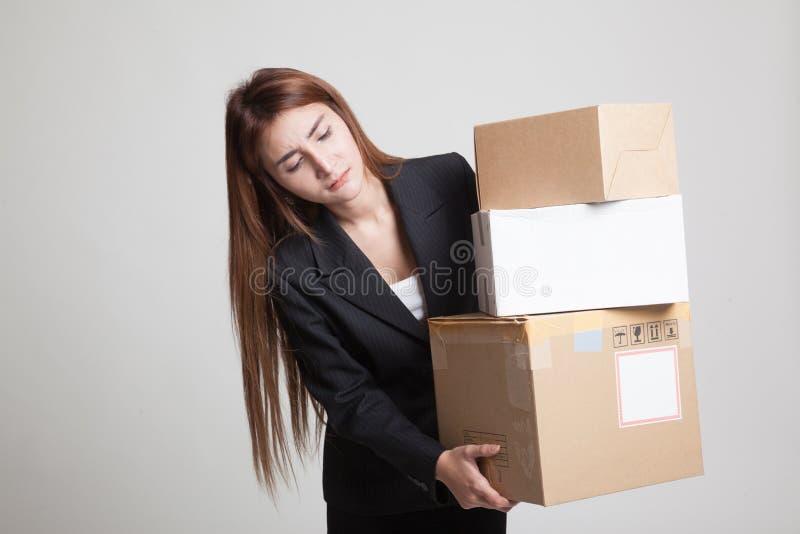 Молодая азиатская работница с 3 тяжелыми коробками доставки стоковое изображение rf