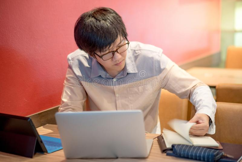 Молодая азиатская тетрадь отверстия бизнесмена пока работающ с подолом стоковое фото