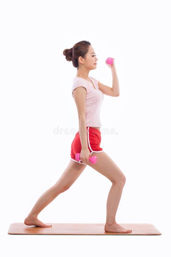 Молодая азиатская тренировка женщины с dubbbell стоковое изображение