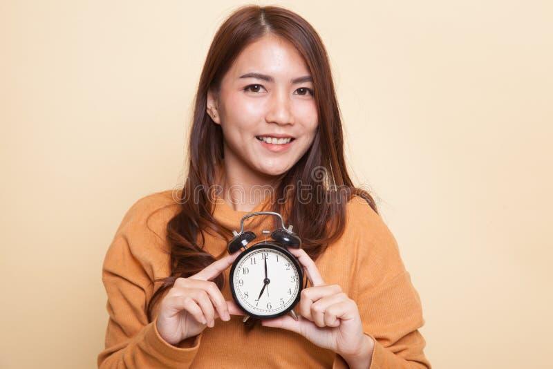 Молодая азиатская улыбка женщины с часами стоковые изображения rf