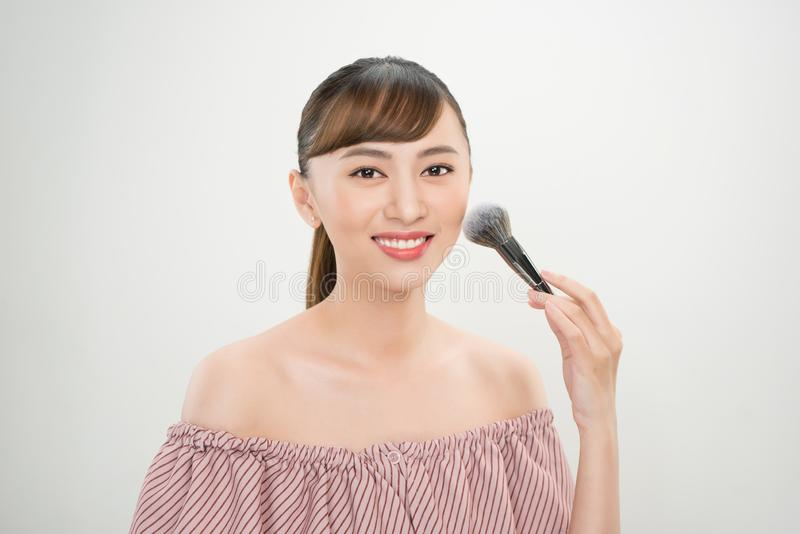 Молодая азиатская щетка макияжа женщины Всход концепции макияжа и косметической процедуры стоковые изображения