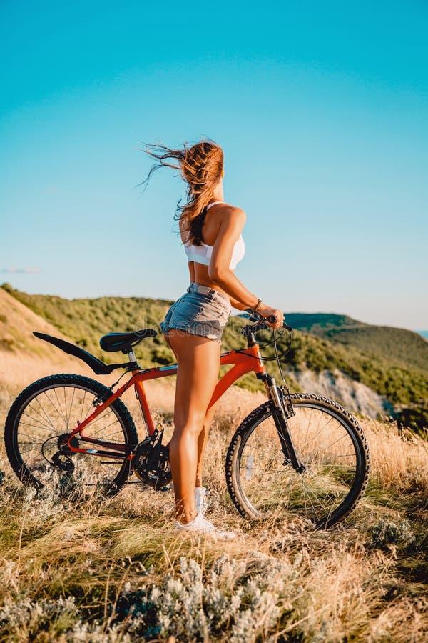 Молодая активная девушка с велосипедом горы в белой рубашке, шортах и белых тапках внешних стоковая фотография