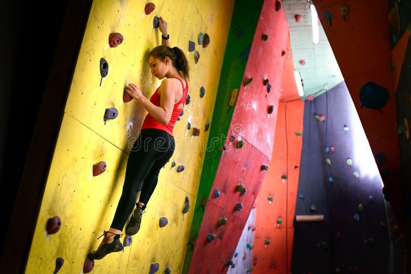 Молодая активная женщина Bouldering на красочном искусственном утесе во взбираясь спортзале Весьма спорт и крытая взбираясь конце стоковые фото