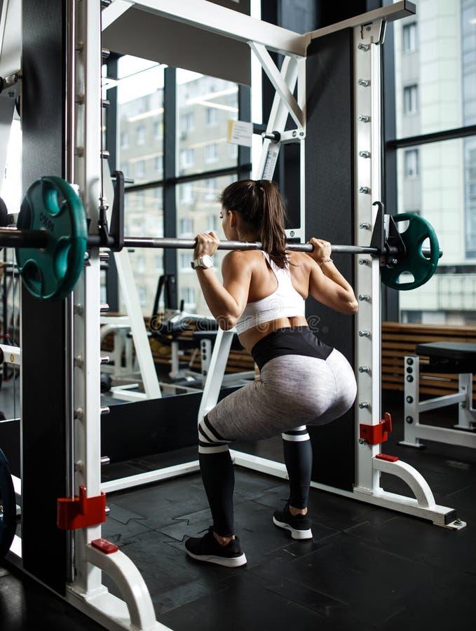 Молодая атлетическая девушка одетая в сидениях на корточках sportswear со штангой в современном спортзале стоковые фото