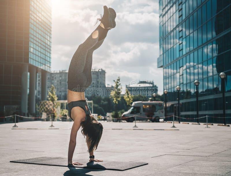Молодая атлетическая женщина делая handstand на улице города среди современных небоскребов разминка Тренировка для баланса, йоги стоковое фото rf