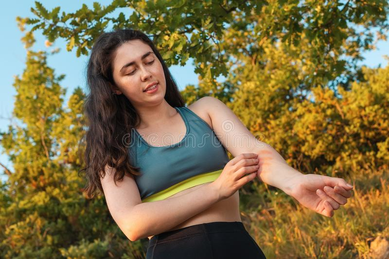 Молодая атлетическая женщина царапает ее руку от укуса насекомого во время тренировки Концепция защиты от укусов насекомого и стоковые фото