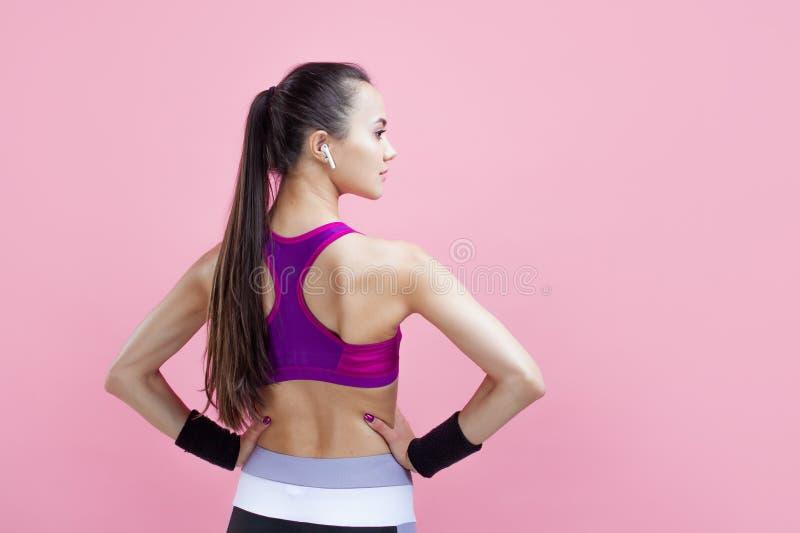 Молодая атлетическая привлекательная девушка с ponytail демонстрирует ее прелестную атлетическую форму с руками на талии, задним  стоковые изображения