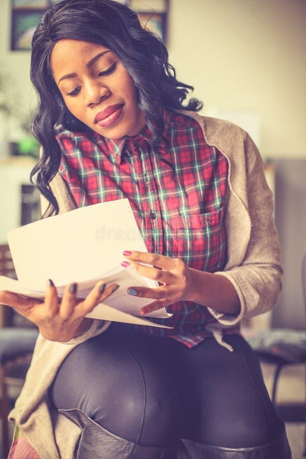 Молодая африканская бизнес-леди на кафе, проверяя документы стоковая фотография