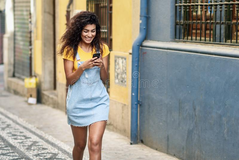 Молодая африканская девушка идя на улицу смотря ее умный телефон Усмехаясь арабская женщина в случайных одеждах с черное курчавым стоковое изображение