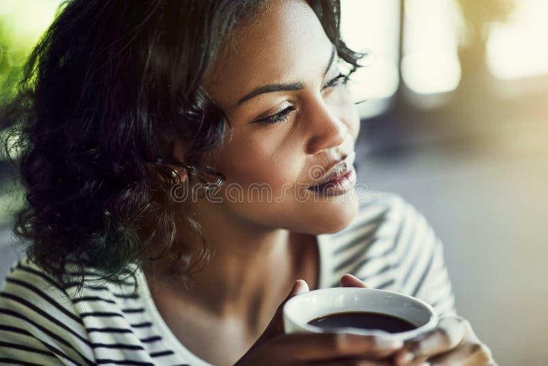 Молодая африканская женщина выпивая кофе смотря глубоко в мысли стоковое изображение rf