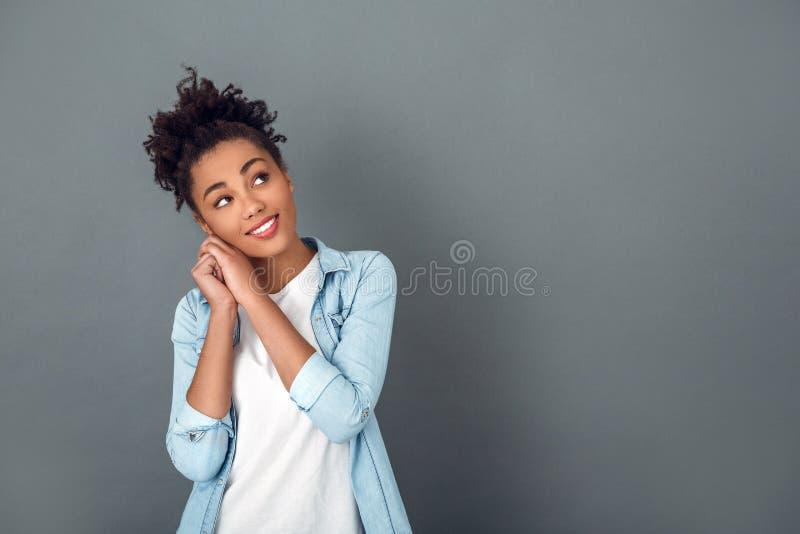 Молодая африканская женщина изолированная на мечтать образа жизни серой студии стены вскользь ежедневный стоковая фотография rf