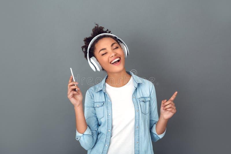 Молодая африканская женщина изолированная на музыке серого образа жизни студии стены вскользь ежедневного слушая стоковые фотографии rf