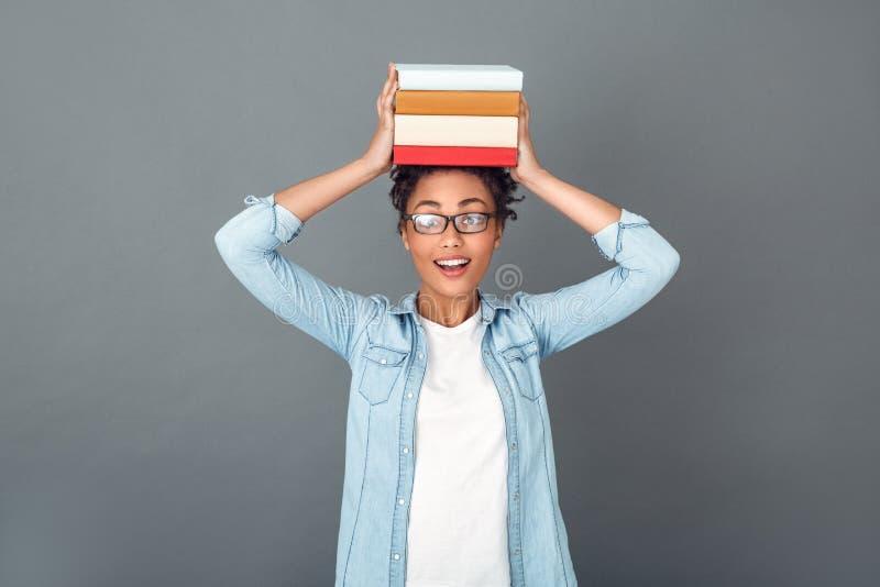 Молодая африканская женщина изолированная на студенте образа жизни серой студии стены вскользь ежедневном держа кучу книг стоковая фотография rf