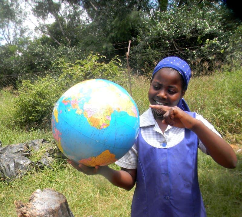 Молодая африканская основная школьница с картой глобуса мира в руке стоковое фото rf