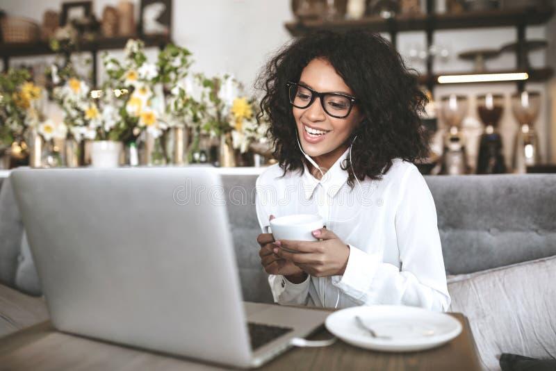 Молодая Афро-американская девушка в стеклах сидя в ресторане с компьтер-книжкой и чашкой кофе в девушке рук усмехаясь с стоковые фотографии rf