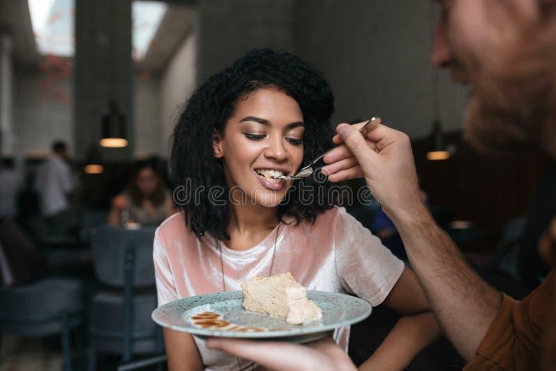 Молодая Афро-американская девушка с темным вьющиеся волосы есть торт в ресторане Портрет молодого человека подавая его подруга стоковое фото