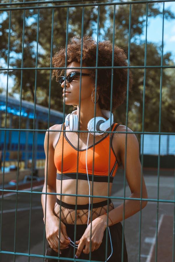 молодая Афро-американская женщина в sportive одежде и солнечных очках стоя на суде спорт с наушниками вокруг стоковое фото