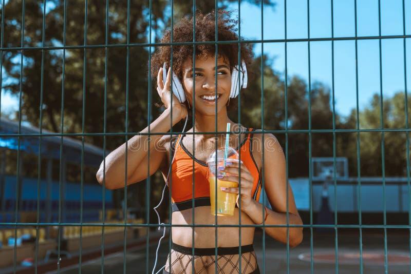 молодая Афро-американская женщина в sportswear слушая к музыке в наушниках и выпивать стоковые изображения rf
