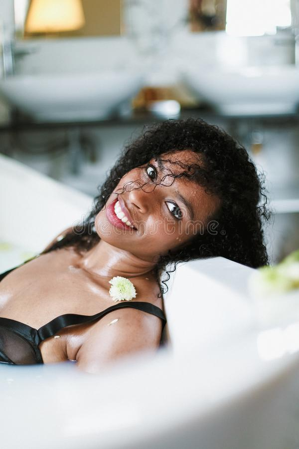 Молодая афро американская женщина ослабляя в ванне с цветком на плече, нося черном купальнике Концепция спа и личное стоковые фото