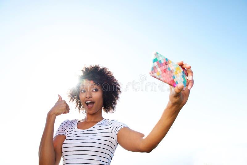 Молодая Афро-американская женщина принимая selfie с мобильным телефоном стоковые фото