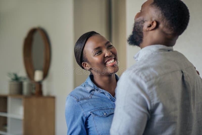 Молодая Афро-американская женщина смеясь с ее супругом дома стоковая фотография