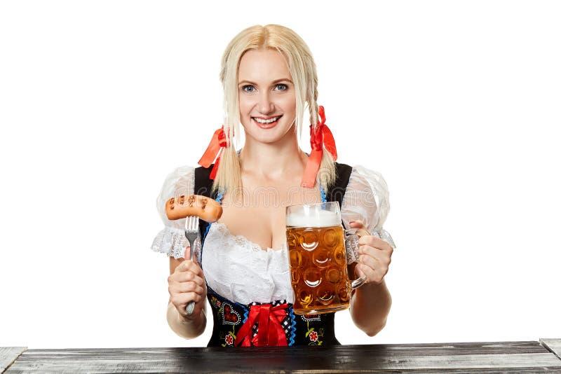 Молодая баварская женщина в dirndl сидя на таблице с пивом на белой предпосылке стоковые изображения