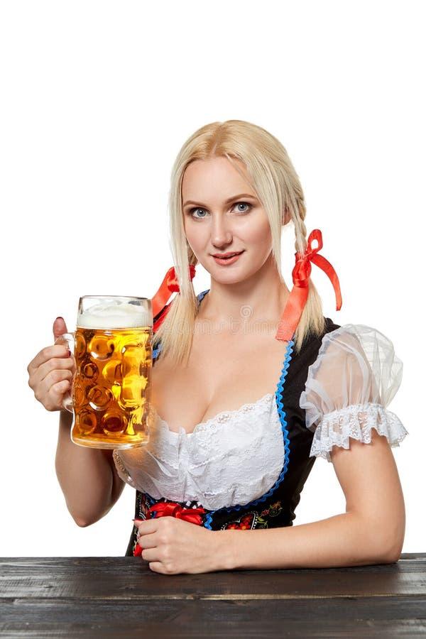 Молодая баварская женщина в dirndl сидя на таблице с пивом на белой предпосылке стоковое изображение