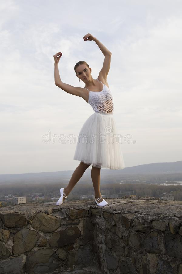 Молодая балерина в белых ботинках балета платья и сатинировки представляя на краю старой крепостной стены на серой предпосылке не стоковое фото rf