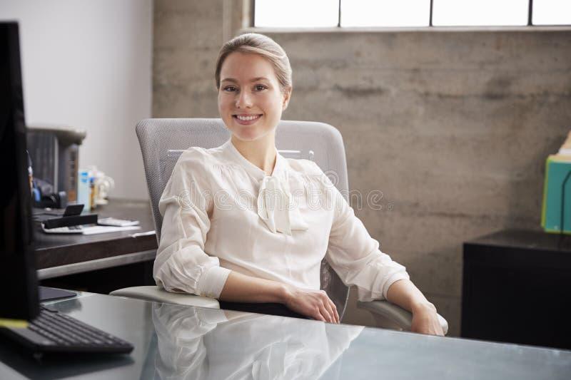 Молодая белая женщина сидя на столе офиса усмехаясь к камере стоковое фото