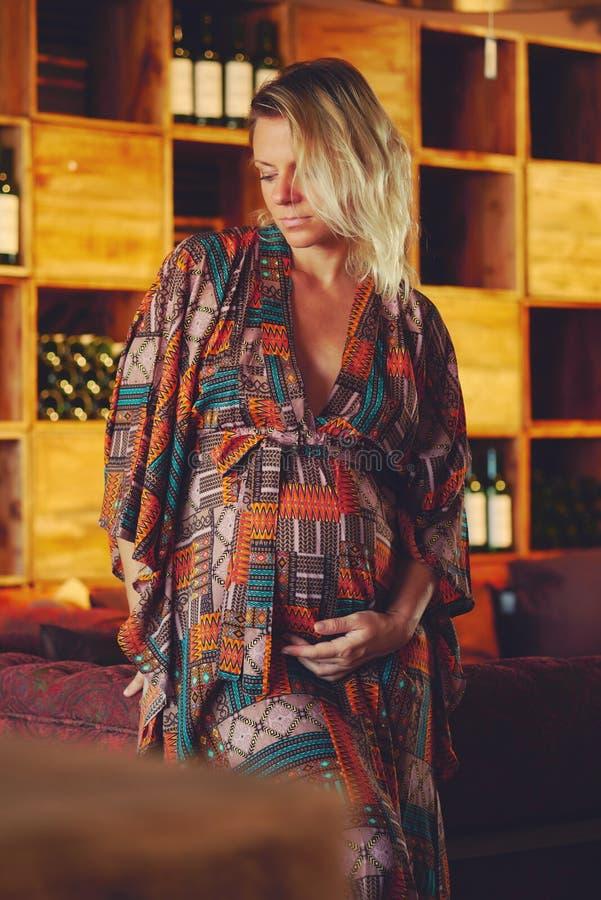 Молодая белокурая беременная женщина касаясь ее животу и смотря прочь стоковые изображения rf