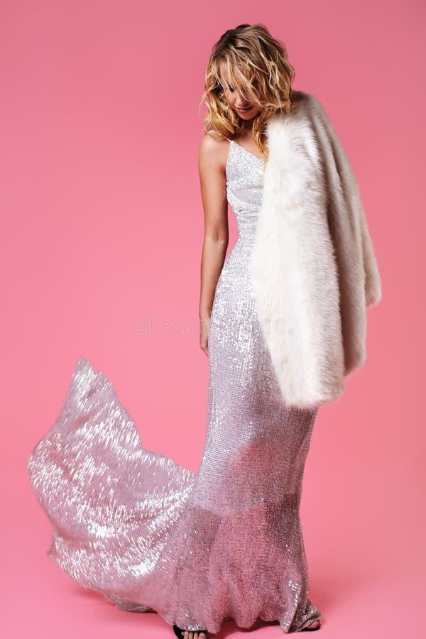Молодая белокурая дама в платье моды, меховой шыбе Сексуальная женщина представляя на розовой предпосылке в роскошных модных одеж стоковые фотографии rf