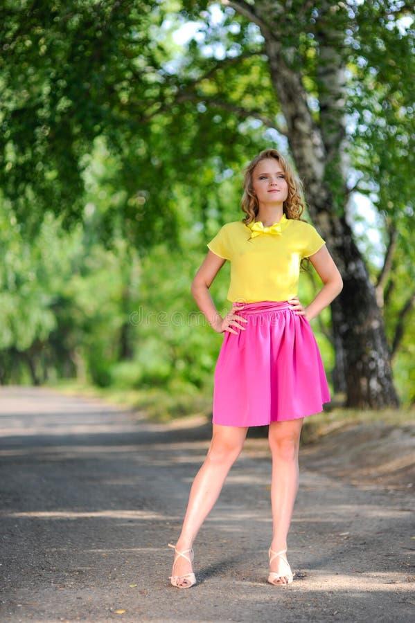 Молодая белокурая девушка в желтой блузке при яркая розовая юбка представляя в парке лета стоковые фото
