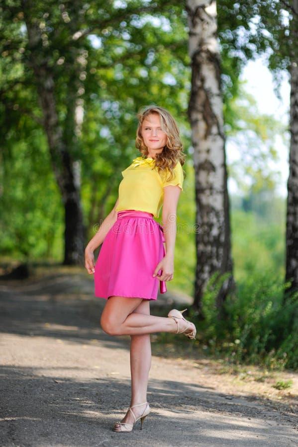 Молодая белокурая девушка в желтой блузке при яркая розовая юбка представляя в парке лета стоковые фотографии rf