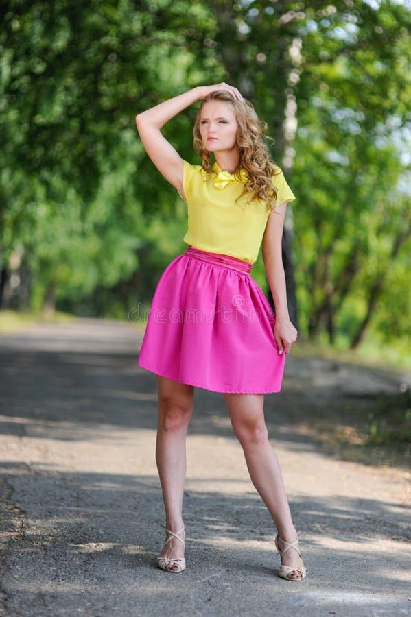 Молодая белокурая девушка в желтой блузке при яркая розовая юбка представляя в парке лета стоковое изображение