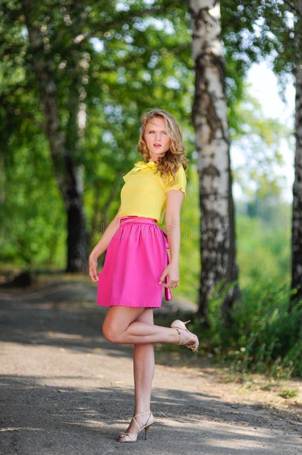 Молодая белокурая девушка в желтой блузке при яркая розовая юбка представляя в парке лета стоковая фотография
