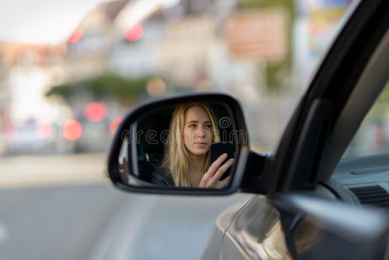 Молодая белокурая девушка в зеркале крыла автомобиля стоковая фотография rf